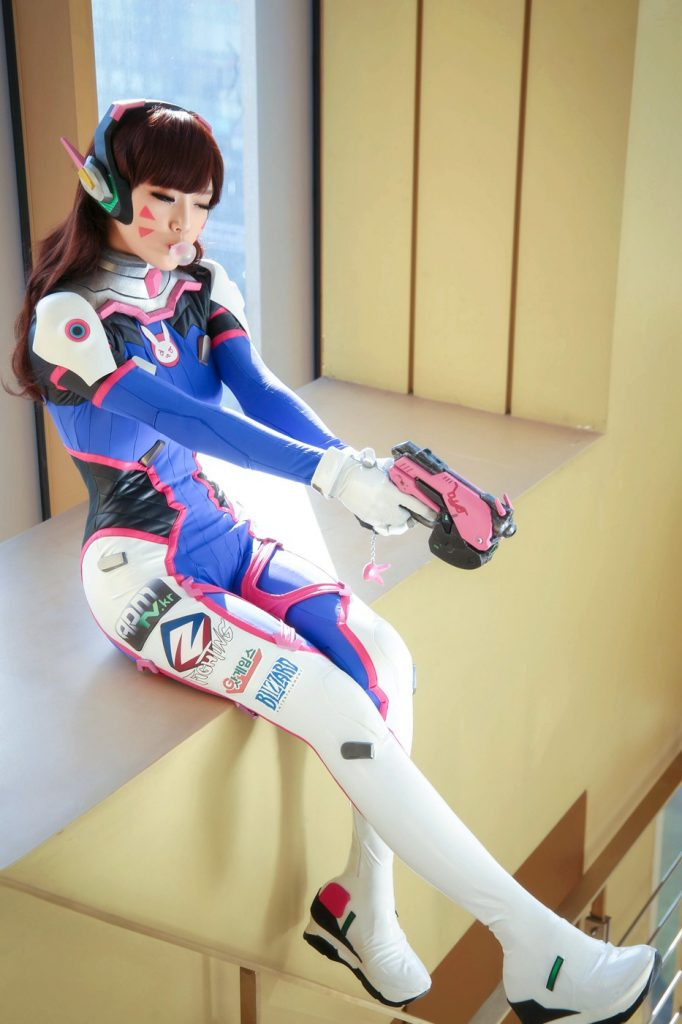 DVA cosplay pointing gun and blowing a bubble
